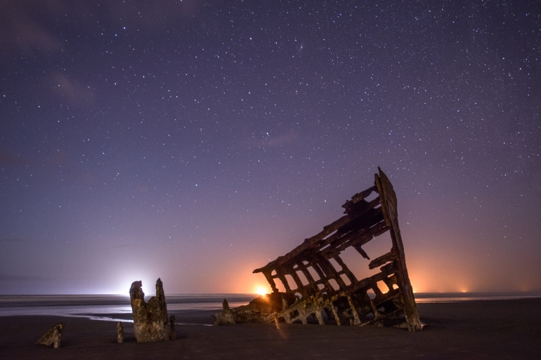 Nikon D800, 14-24mm f/2.8 lens @24mm, f/4, 30 seconds, ISO 1600. The moon lit the foreground, while ships on the horizon added a glow to the foreground elements.